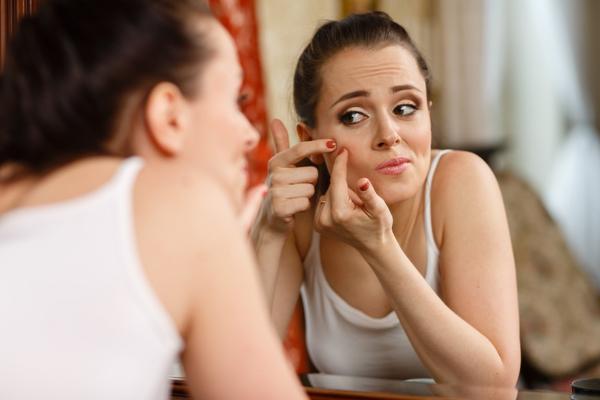 fiatal kány a tükör előtt nyomja ki a pattanását