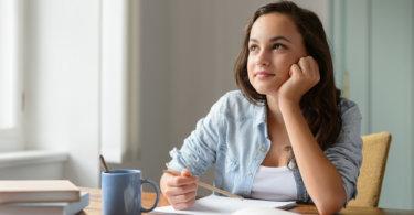 álmodozó lány üll az asztalnál