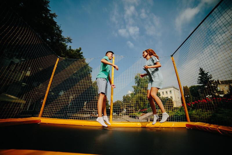 egy fiú és egy lány trambulinban ugrál